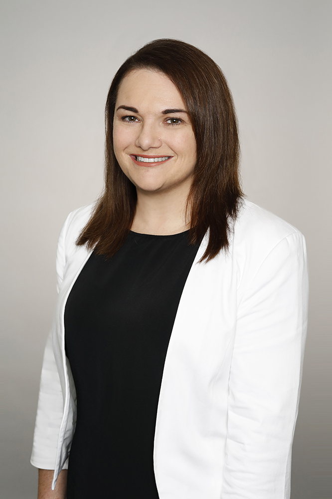 Professional bio photo of Sonia Cahill. She is wearing a navy top and white jacket.